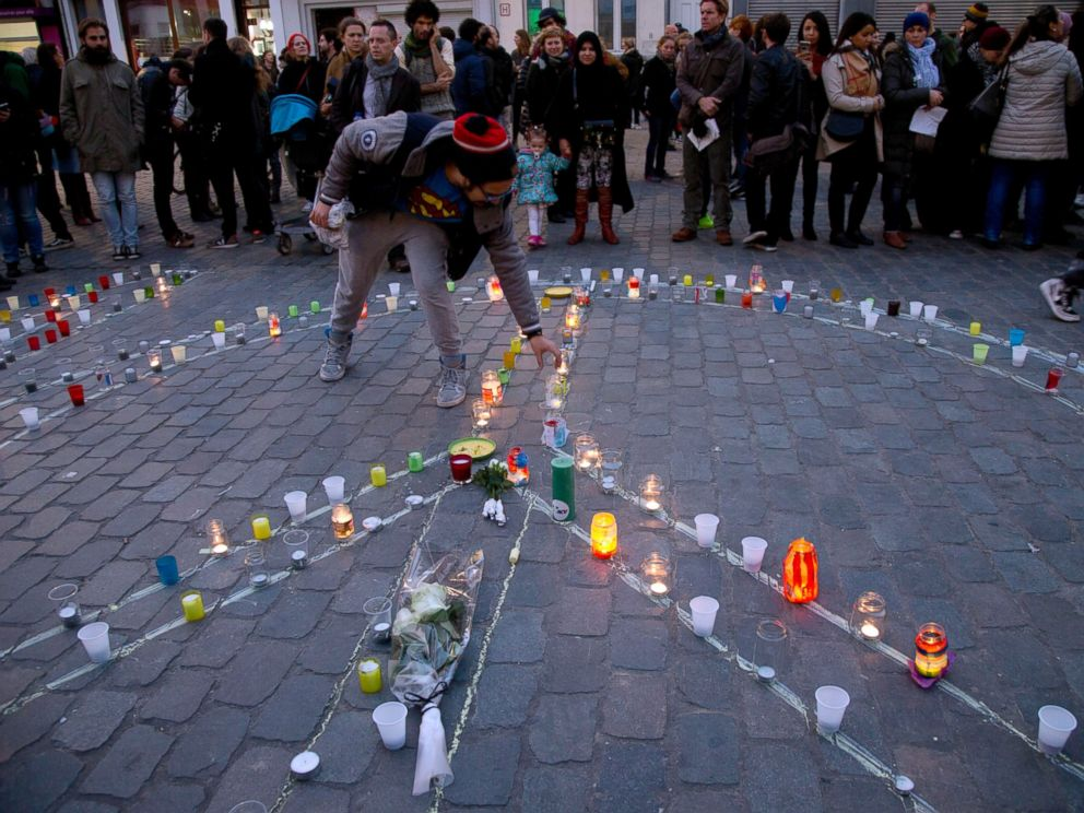 PHOTO: A man lights a candle which forms a peace sign during a candlelight vigil for the Paris attacks in the town square of Molenbeek, Belgium, Nov. 18, 2015.