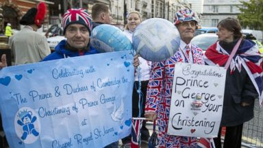 PHOTO: Royal wellwishers gather and display their home made placards and greetings to the media,  as they wait outside St Jamess Palace, for the christening of Britains Prince George, in London on Oct. 23, 2013.