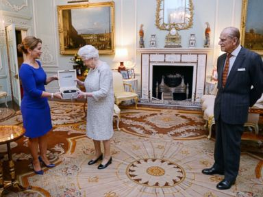 PHOTO: Queen Elizabeth II is presented with a lifetime achievement award for her devotion to equestrian sport by Princess Haya of Jordan as the Duke of Edinburgh looks on, at Buckingham Palace, London on Nov. 26, 2014.