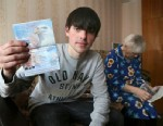 PHOTO: In this photo taken on March 20, 2013, Alexander Abnosov shows his American passport to journalists in the Volga river city of Cheboksary, Russia with his 72 -years old grandmother is in the background.
