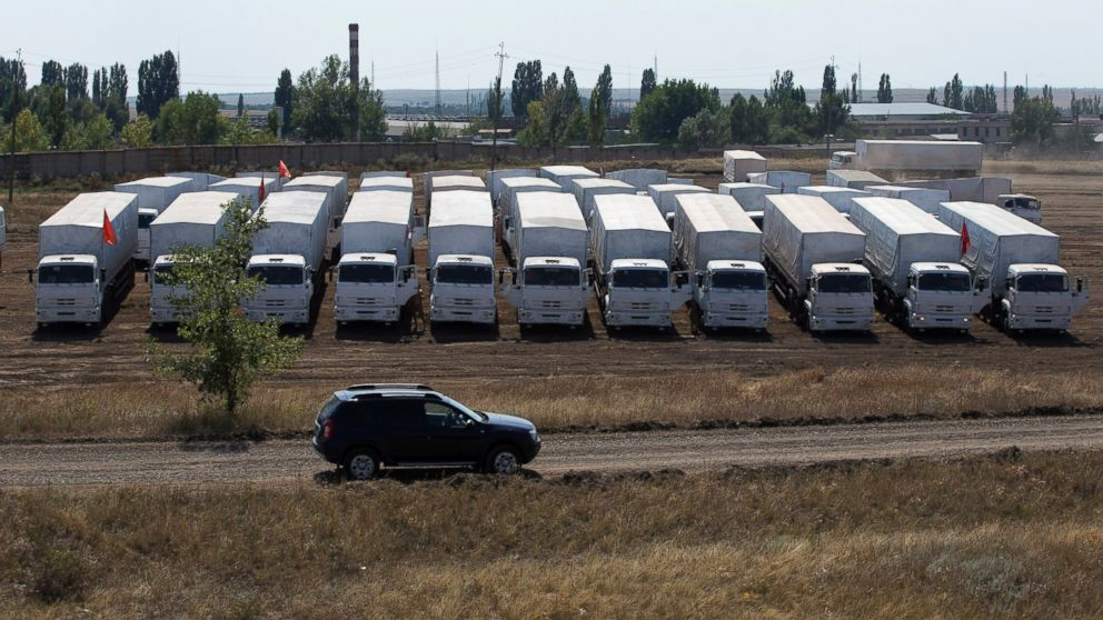 PHOTO: A convoy of white trucks with humanitarian aid sits parked in a field about 28 kilometers from the Ukrainian border in Russia, on Aug. 14, 2014.
