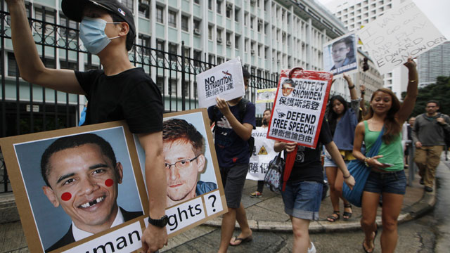 PHOTO: A supporter holds a picture of U.S. President Barack Obama and Edward Snowden, a former CIA employee who leaked top-secret information about U.S. surveillance programs during a demonstration outside the Consulate General of the United States in Hon