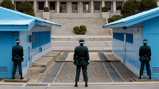 PHOTO: A North Korean soldier, center top, looks at the southern side as South Korean soldiers stand guard at the border village of Panmunjom, which has separated the two Koreas since the Korean War, in Paju, north of Seoul, South Korea on April 10, 2013.