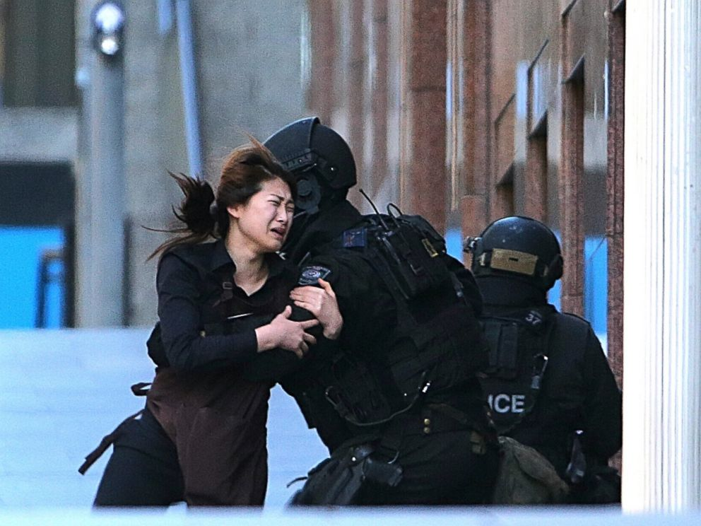 PHOTO: A hostage runs to armed tactical response police officers for safety after she escaped from a cafe under siege at Martin Place in the central business district of Sydney, Australia, Dec. 15, 2014.
