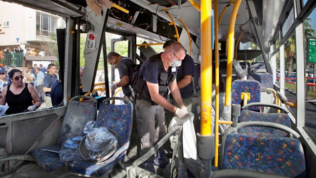 PHOTO: Israeli police officers examine a destroyed bus at the site of a bombing in Tel Aviv, Israel, Nov. 21, 2012.