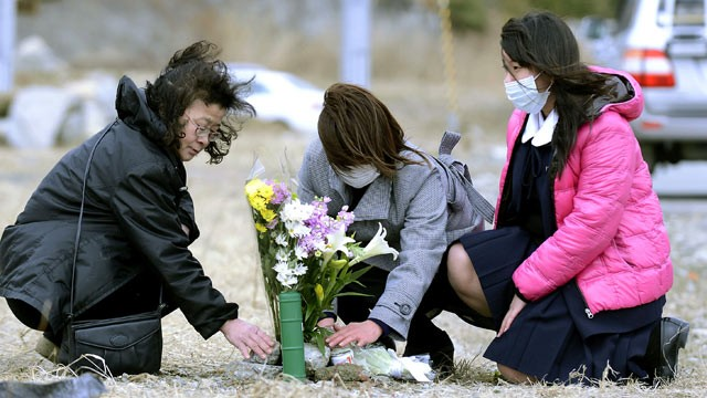 PHOTO: Yoko Yasuda, center, offers flowers where her parents' house used to stand in Rikuzentakata, Iwate prefecture, northern Japan, March 10, 2013.