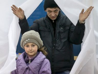 PHOTO: A man and child exit a voting booth after casting a vote in the Crimean referendum in Simferopol, Ukraine, Sunday, March 16, 2014.