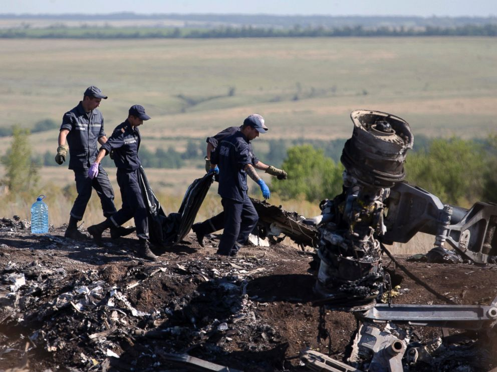 PHOTO: Ukrainian Emergency workers carry a victims body in a plastic bag at the crash site of Malaysia Airlines Flight 17 near the village of Hrabove, Donetsk region, eastern Ukraine, July 21, 2014.