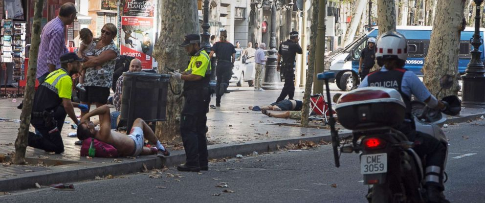 PHOTO: Police officers attend to injured people after a van crashed into pedestrians on Las Ramblas in downtown Barcelona, Aug. 17, 2017.