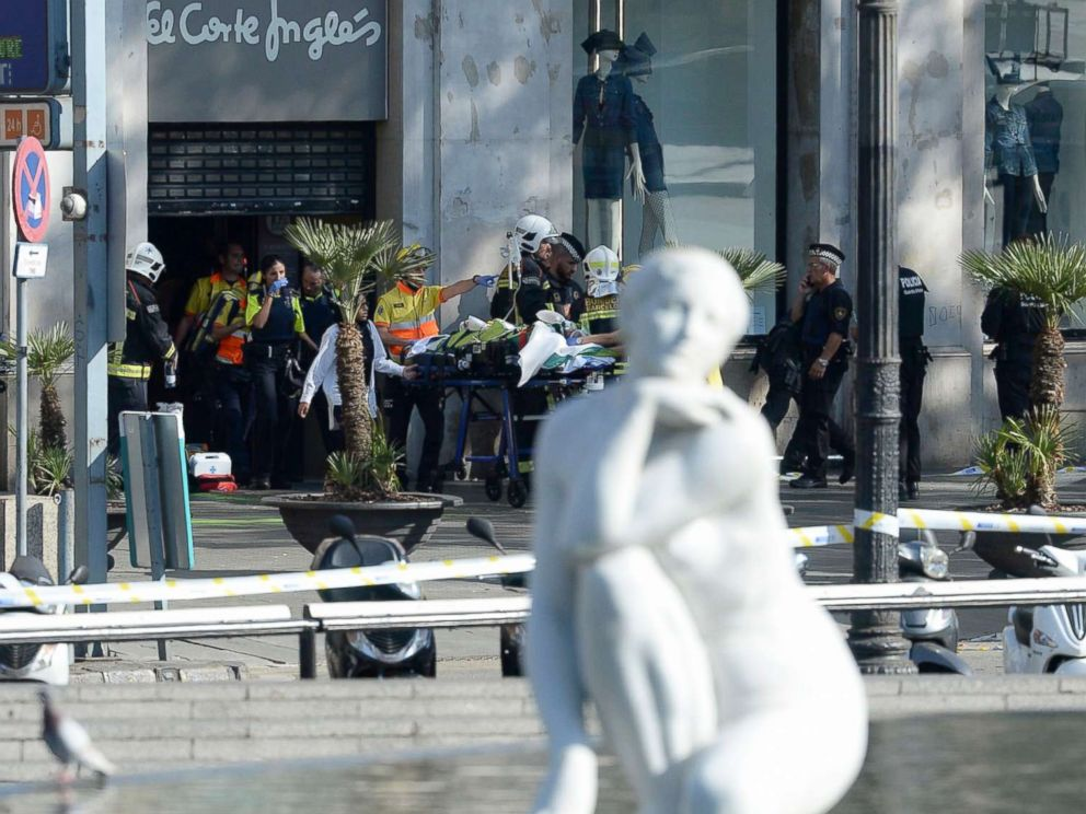 PHOTO: A person is stretched out of a mall by medical staff members in a cordoned off area after a van ploughed into the crowd, injuring several persons on the Rambla in Barcelona, Aug. 17, 2017.
