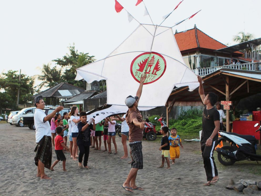 PHOTO: Girls and boys from the projects pilot village, Pererenan, help fly a giant kite carrying the Bye Bye Plastic Bags logo, to increase awareness, Bali, Indonesia.