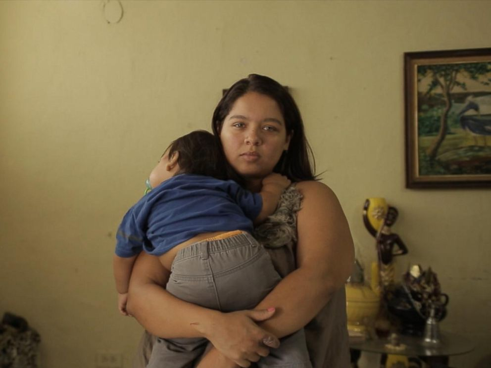 PHOTO: A young anti-government demonstrator at home with her son, Venezuela.
