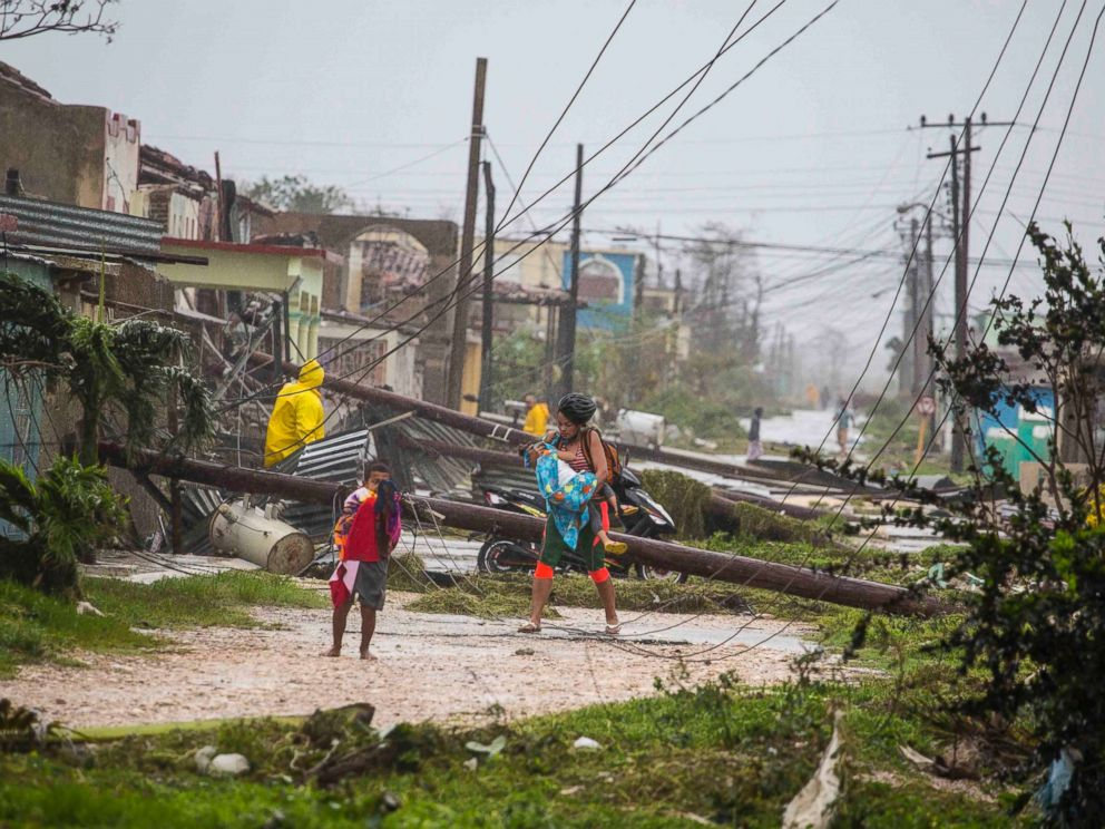 PHOTO: Residents walk near downed power lines felled by Hurricane Irma, in Caibarien, Cuba, Sept. 9, 2017.