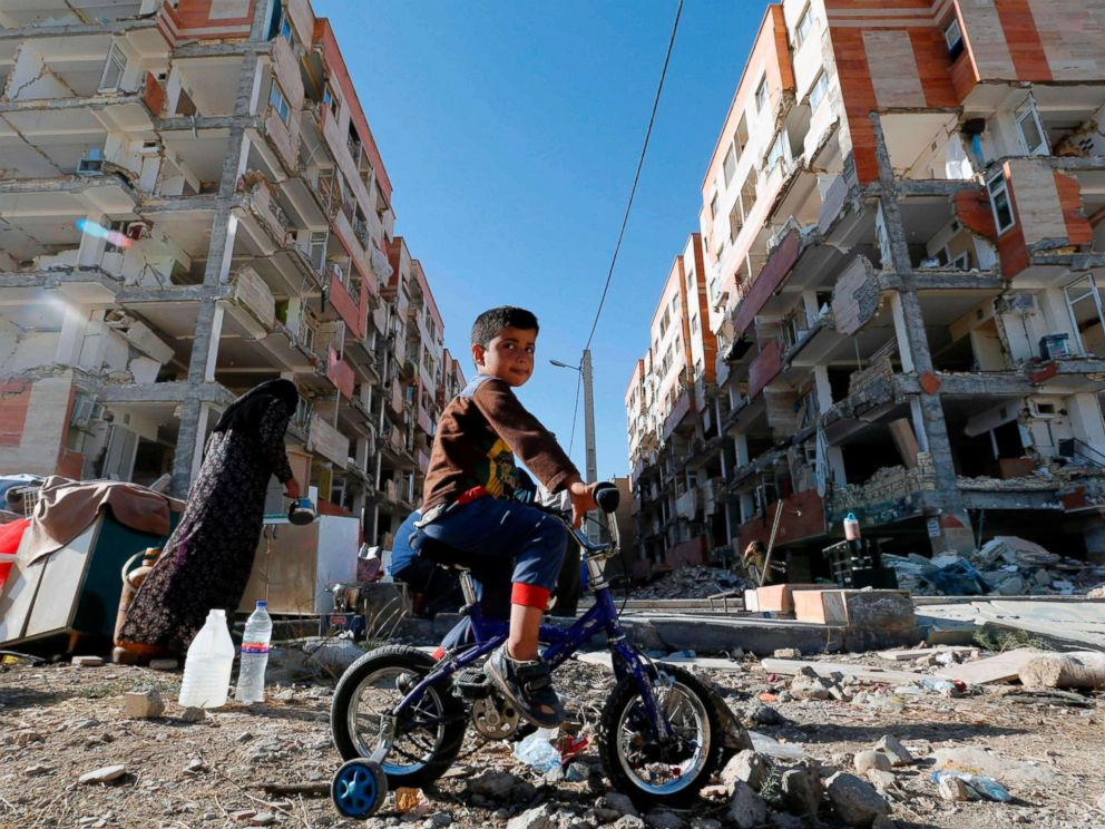PHOTO: A boy rides a bicycle past earthquake damaged buildings in the town of Sarpol-e Zahab in Irans western Kermanshah province near the border with Iraq, Nov. 14, 2017. A powerful earthquake struck the region on Nov. 12.