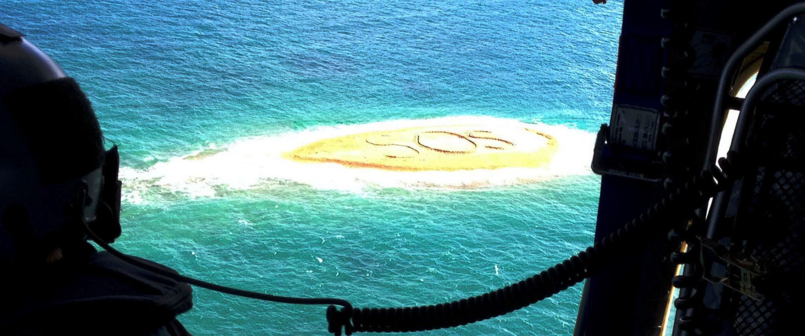 PHOTO: A handout image released by the Royal Australian Automobile Club of Queensland (RACQ) on shows a view from a RACQ Rescue helicopter showing a giant SOS message on a sandbar near Brampton Island, Queensland, Australia, on April 21, 2014.