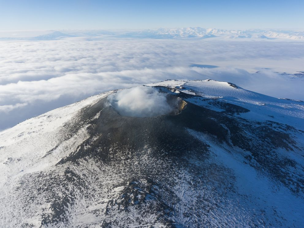 PHOTO: The crater of Mount Erebus is viewed from helicopter as steam is emitted from the molten lava lake a few hundred feet beneath the crater rim. In the background are the Transantarctic Mountains, one of the longest mountain chains in the world.