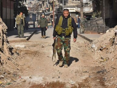 PHOTO: Syrian pro-government forces walk through a barricade in old Aleppos Jdeideh neighborhood, Dec. 9, 2016. Syrias government has retaken at least 85 percent of east Aleppo, which fell to rebels in 2012.