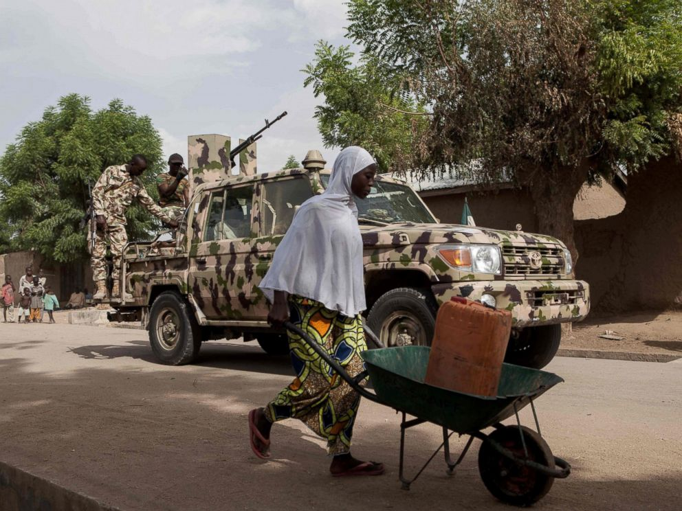 PHOTO: A woman pushes a wheelbarrow carrying a jerrycan filled with water as Nigerian soldiers patrol in the town of Banki in northeastern Nigeria, April 26, 2017.