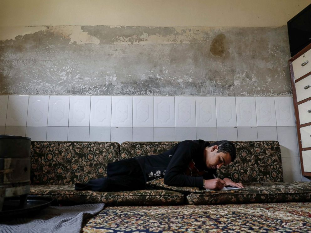 PHOTO: Mute 17-year-old Syrian Adnan, who lost both legs in 2014 following an airstrike as he was walking towards his fathers store from school, does his homework at his home, in Douma, on the outskirts of the capital Damascus, Feb. 16, 2017.