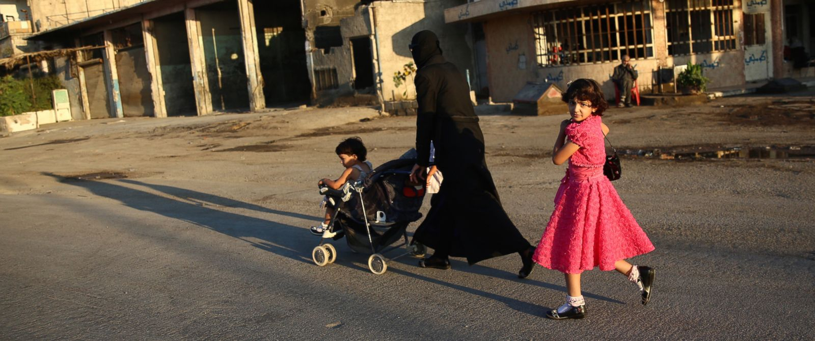 PHOTO: A Syrian girl walks with her mother in the rebel-held town of Douma east of the capital Damascus, July 6, 2016.
