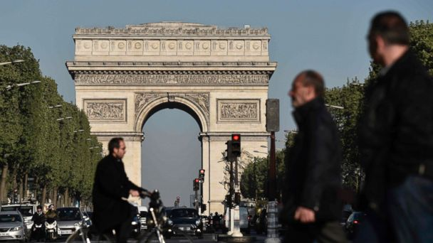PHOTO: Pedestrians and vehicles take the Champs Elysees avenue near the Arc de Triomphe monument in Paris, April 21 ,2017, a day after a gunman opened fire on police on the avenue..