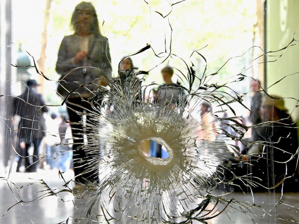 PHOTO: People look at a bullet hole in a window near to the Marks and Spencer on the Champs Elysees in Paris following the shooting of a police officer on April 21, 2017.