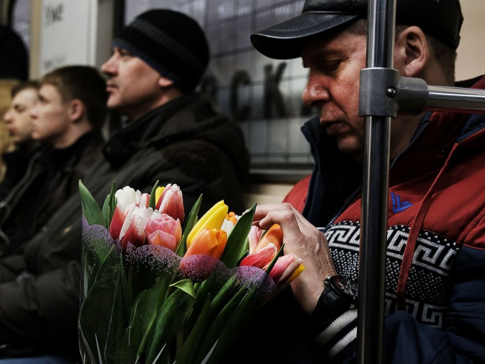 PHOTO: A man holds flowers while riding a Moscow subway on March 6, 2017.