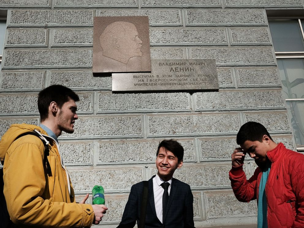 PHOTO: Students stand under a picture of Vladimir Lenin in downtown Moscow on March 9, 2017.