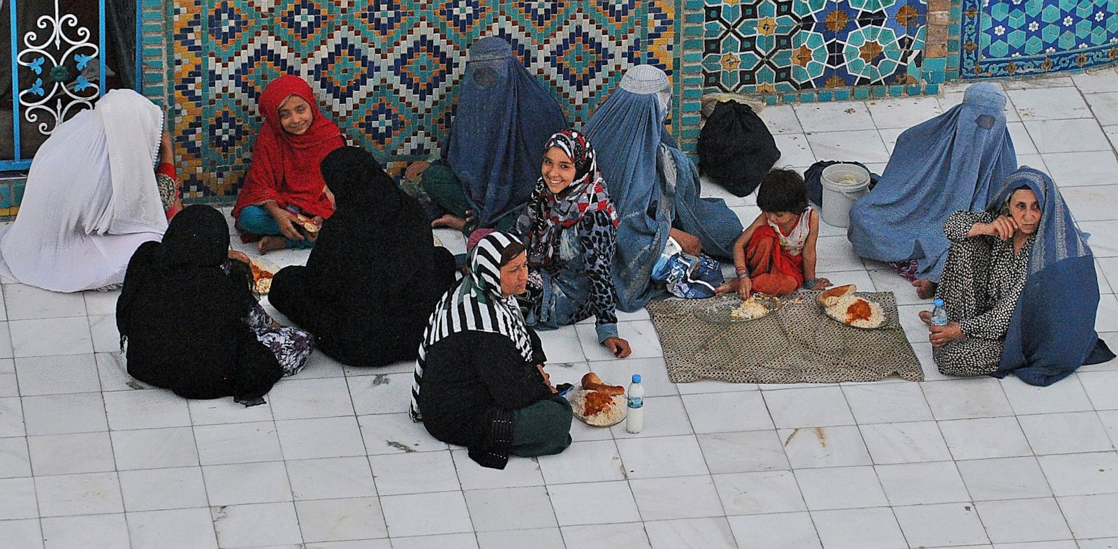 PHOTO: Afghan women wait to break their fast during the holy month of Ramadan at the Hazrat-e Ali shrine in Mazar-i Sharif in northern of Afghanistan on July 17, 2013.