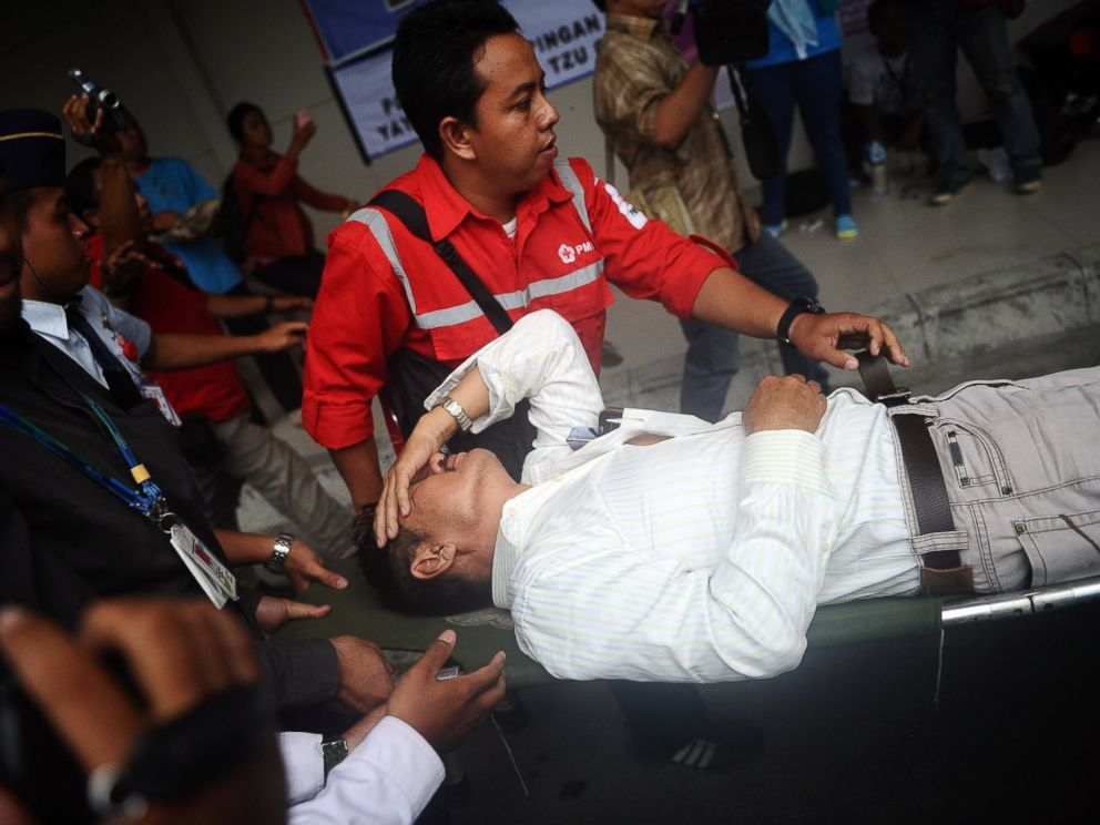 PHOTO: A relative of passengers on AirAsia flight QZ 8501 receives medical attention as he collapses at the breaking news of debris and bodies being found on Dec. 30, 2014 in Surabaya, Indonesia.