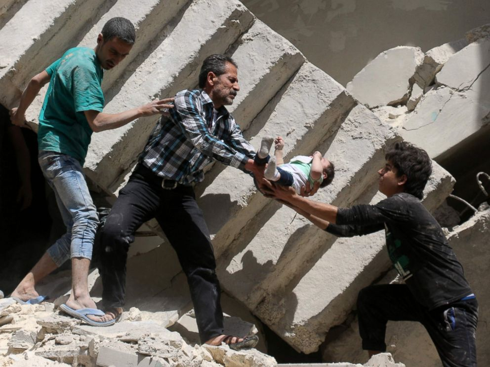 PHOTO: Syrian civil defense volunteers and rescuers remove a baby from under the rubble of a destroyed building following an air strike on the rebel-held neighborhood of al-Kalasa in the northern Syrian city of Aleppo, on April 28, 2016.