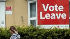 PHOTO: A woman walks past a house where Vote Leave boards are displayed in Redcar, England, June 27, 2016.
