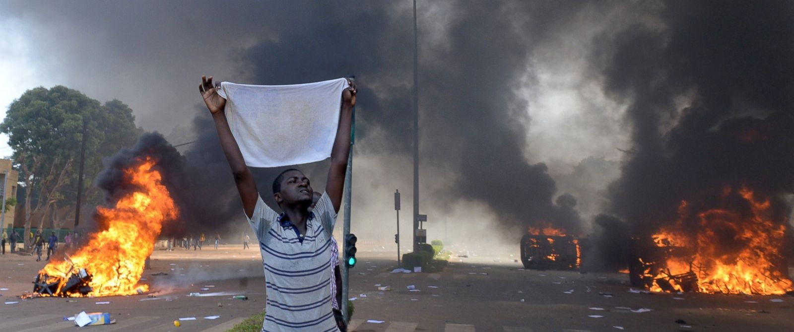 PHOTO: A protester holds a white cloth as cars and documents burn outside the parliament in Ouagadougou, Burkina Faso, Oct. 30, 2014.