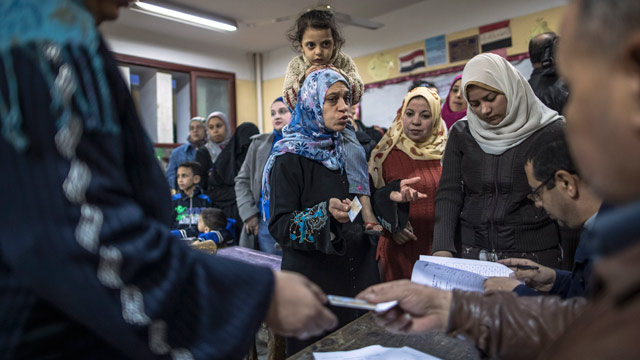 PHOTO: A woman carrying her daughter vents her frustrations to electoral staff as she and others wait to cast their vote during a referendum on the new Egyptian constitution at a polling station on Dec. 15, 2012 in Cairo, Egypt.