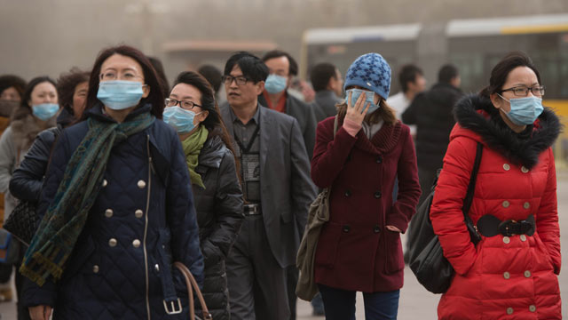 PHOTO: People wearing face masks walk near the Forbidden City during heavy pollution in Beijing on Feb. 28, 2013.