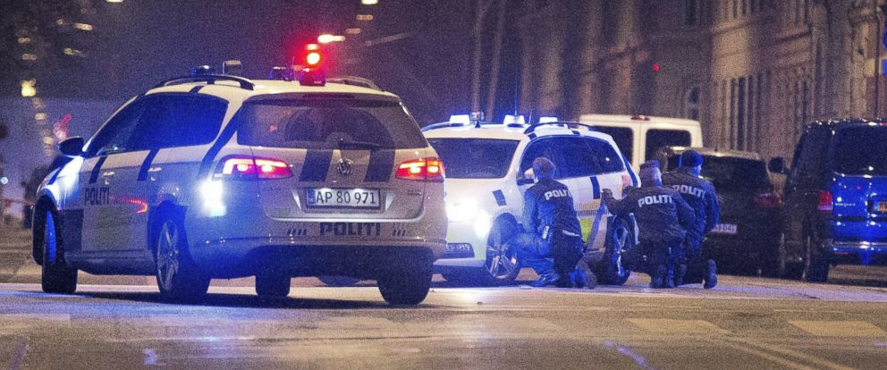 PHOTO: Police officers take cover on the streets of Copenhagen on Feb. 15, 2015 after one person was shot in the head and two policemen were shot in the arm and leg in Krystalgade, a street that is home to Copenhagens main synagogue.