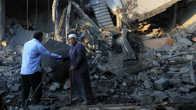 PHOTO: Palestinians walk past the debris of a destroyed home following an Israeli air strike in Gaza City, on November 19, 2012.