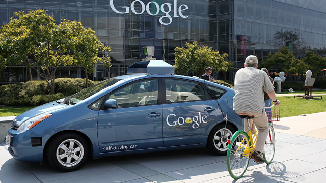 PHOTO: A bicyclist rides by a Google self-driving car at the Google headquarters on September 25, 2012 in Mountain View, California.