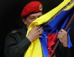 PHOTO: Venezuelan President Hugo Chavez kisses a Venezuelan national flag at Miraflores presidential palace in Caracas, July 4, 2011.