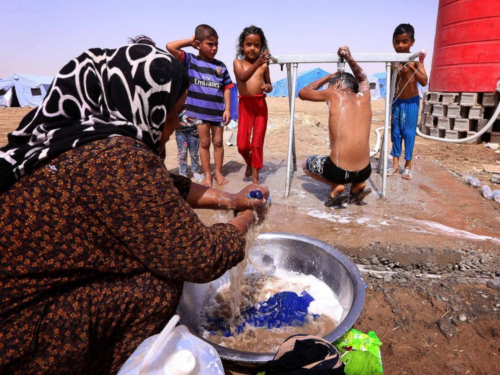 PHOTO: A displaced Iraqi woman washes her familys laundry as children shower outside their tent at a temporary camp set up to shelter civilians fleeing violence in Iraqs northern Nineveh province on June 13, 2014.