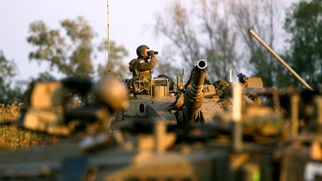 PHOTO: An Israeli soldier looks through binoculars from the top of his Merkava tank during a drill near the border with Syria at the Israeli-annexed Golan Heights, May 6, 2013.