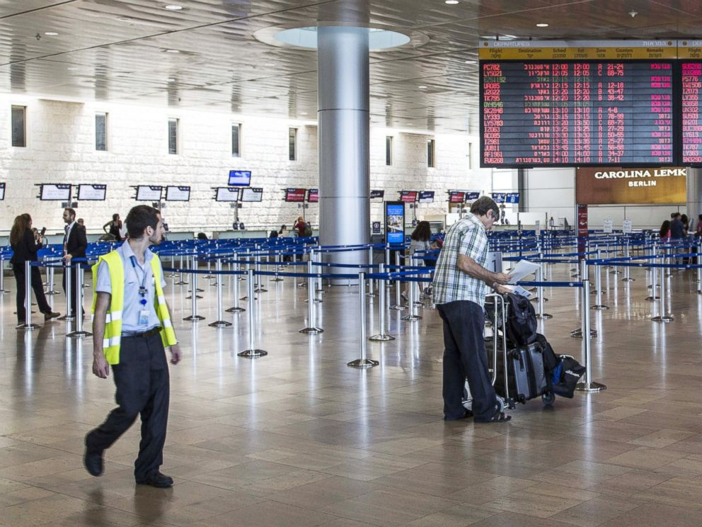 PHOTO: Israeli passengers walk near a departure time flight board displaying various cancellations at Ben Gurion International airport, near Tel Aviv, on July 23, 2014.