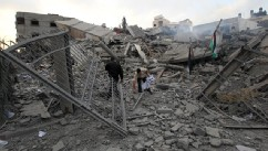 PHOTO: Palestinian Hamas security members inspect the destroyed office building of Hamas Prime Minister Ismail Haniya in Gaza City on November 17, 2012.