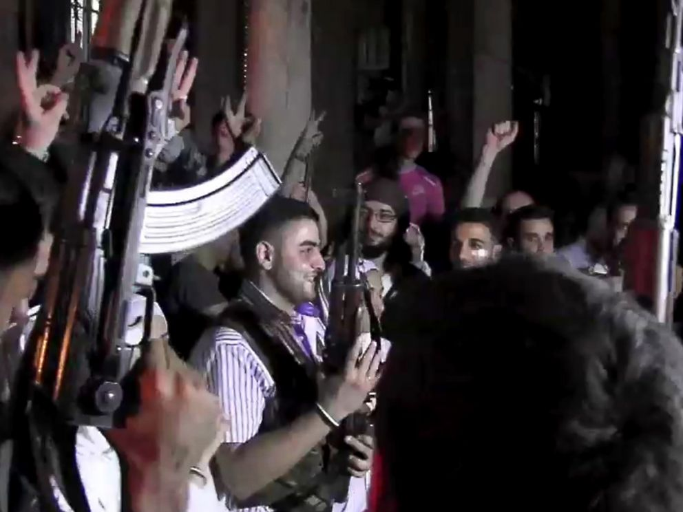 PHOTO: An image grab taken from AFP TV shows Syrian rebel sniper Abu Khaled (C) holding his gun as comrades celebrate during his wedding ceremony in Aleppo on August 31, 2012.