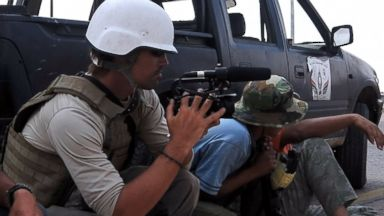 PHOTO: A photo taken on September 29, 2011 shows US freelance reporter James Foley (L) on the highway between the airport and the West Gate of Sirte, Libya.