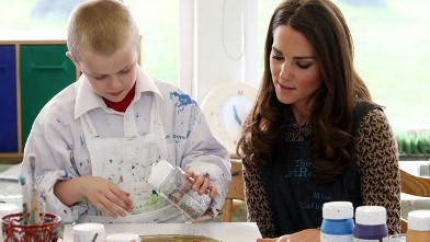 PHOTO: Catherine, the Duchess of Cambridge, helps a child with his painting during an official visit to the Art Room facilities at Rose Hill Primary School in Oxford on Feb. 21, 2012.