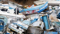PHOTO: Boats damaged by the tsunami following the Great East Japan Earthquake are stacked in a pile in Kesennuma,Miyagi Prefecture, Japan, March 10, 2013.