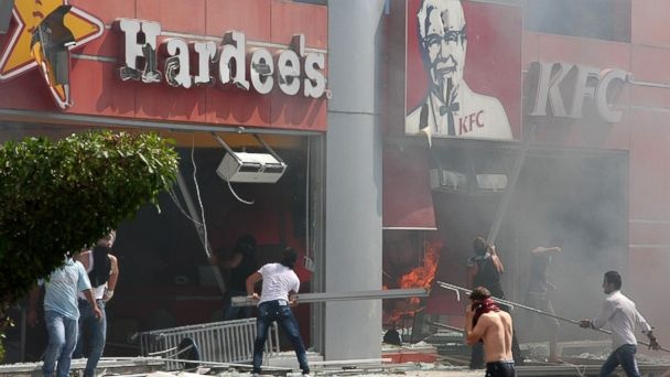 "PHOTO: Lebanese men ransack US fast food chains Hardees and KFC as they protest against the controversial film ""Innocence of Muslims"" in the northern Lebanese city of Tripoli on September 14, 2012."