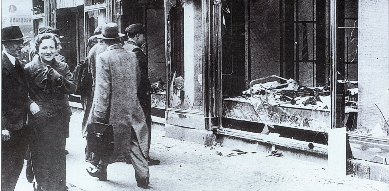 PHOTO: Pedestrians glance at the broken windows of a Jewish owned shop in Berlin after the attacks of Kristallnacht, November 1938.