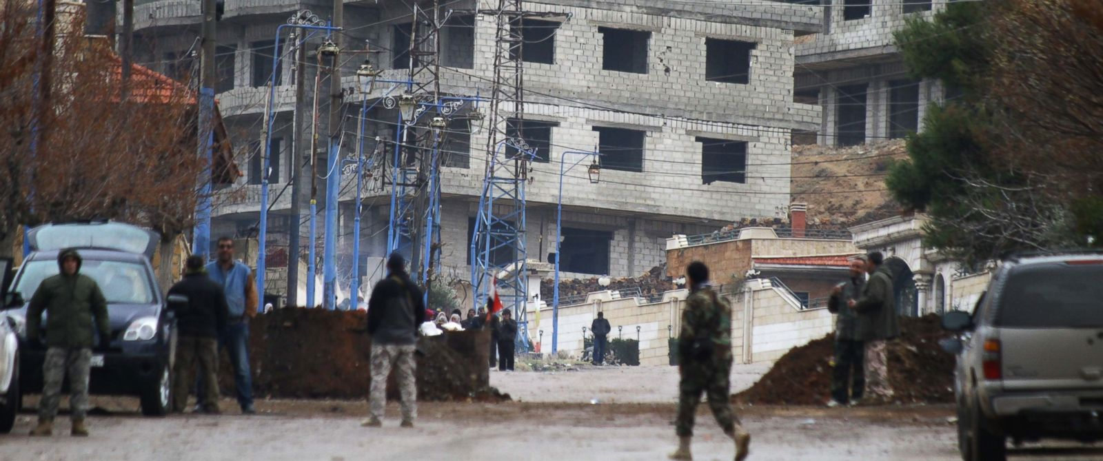 PHOTO: Syrian pro-government forces stand at the entrance of the besieged Syrian town of Madaya as they wait for a convoy of aid from the Syrian Arab Red Crescent on Jan. 14, 2016.